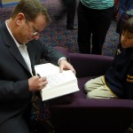 Mark signs for a young fan